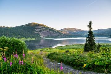 Widok na górskie jezioro ze wzgórzami i zielony las podczas wschodu słońca. Ergaki park narodowy, Syberia, Rosja