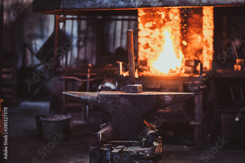 Hammer on anvil at dark blacksmith workshop with fire in stove at background Canvas Print