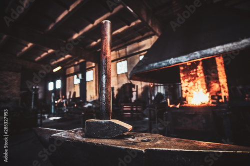 Dark stithy workshop with hammer on anvil at firs plan and fire in stove at background Canvas Print