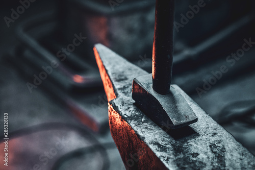 Close up photo shoot of hammer and anvil at dark smith workshop. Canvas Print