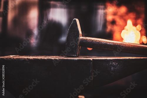 Stampa su Tela Close up photo shoot of hammer and anvil at dark smith workshop.