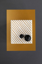 Diagonally Striped Gold And White Christmas Present And Black Ornaments