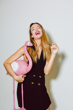 Funny Woman Holding A Flamingo Toy In A New Year Party Celebration.