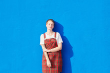 Confident Blonde Girl In Checked Dress At Blue Wall.