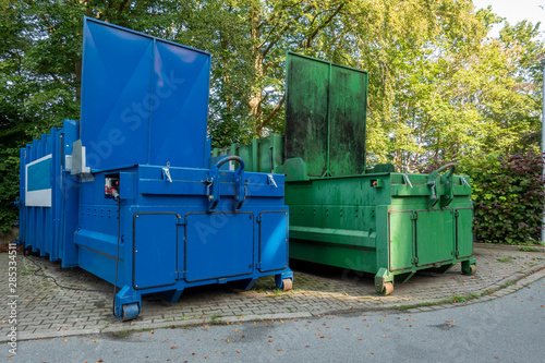 two garbage compactors Standing next to each other on the premises of a hospital Canvas Print