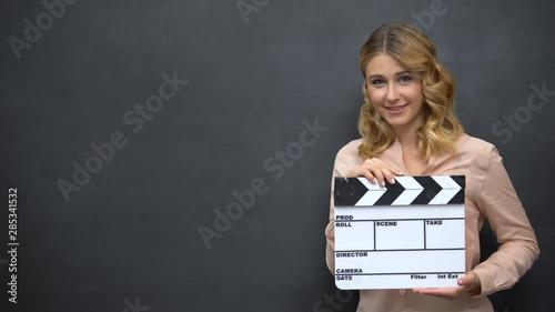 Beautiful girl using clapperboard advertise of acting school film production