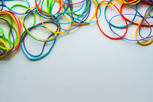 Top View Of Colorful Rubber Bands Isolated On White. Rainbow Elastic Rubber Bands On White