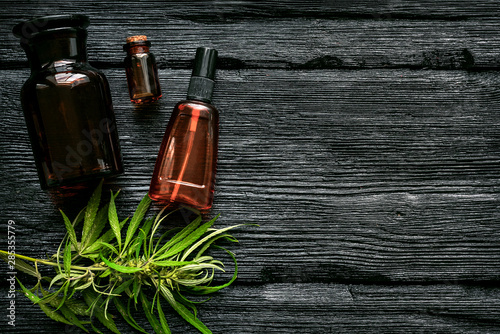 Fototapeta Cannabis cbd oil in bottle and green leaves on a black wooden table flat lay background. obraz