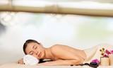 Beautiful young woman receiving hot stone massage at salon spa - 285362793