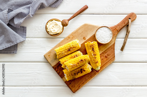 Fototapeta Fried corn on board with salt and butter on white wooden background top view