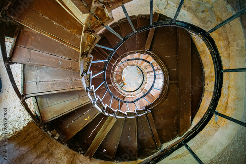 Obraz na plátně Old spiral staircase in abandoned mansion, bottom view