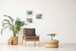 Leinwanddruck Bild - Stylish living room interior with wooden armchair and plants near white wall. Space for text