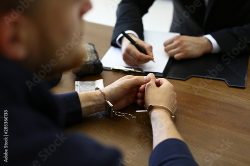 Police officer interrogating criminal in handcuffs at desk indoors Fototapeta