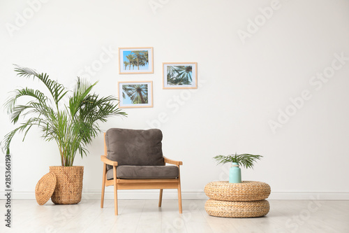 Fotografia, Obraz  Stylish living room interior with wooden armchair and plants near white wall
