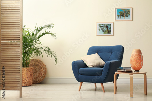 Photo  Stylish room interior with comfortable furniture and plant near beige wall