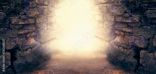 Mysterious fantasy photo background, magical trail leading out through stone dungeon cave walls towards mystical glow Fototapet