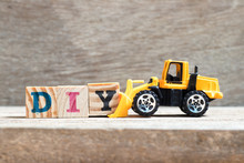 Toy Bulldozer Hold Letter Block Y To Complete Word DIY (abbreviation Of Do It Yourself)  On Wood Background