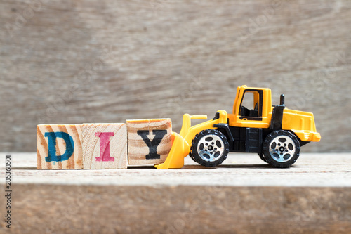 Toy bulldozer hold letter block Y to complete word DIY (abbreviation of do it yo Wallpaper Mural