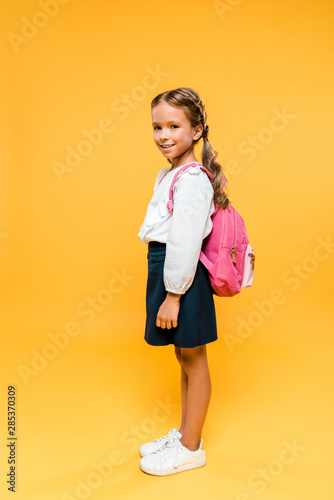 happy schoolkid looking at camera while standing on orange