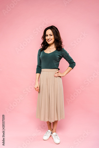attractive woman standing with hand on hip on pink