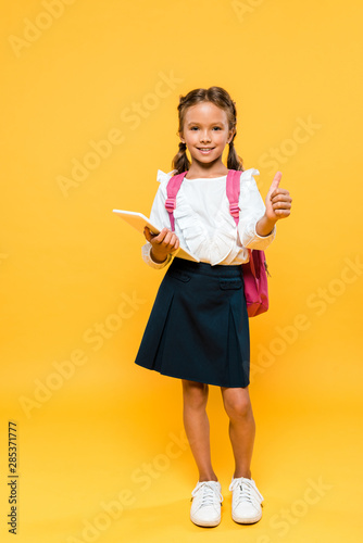 happy schoolkid holding books and showing thumb up on orange
