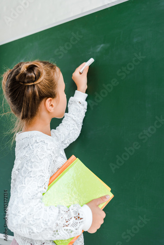 cute schoolkid holding chalk and books near green chalkboard