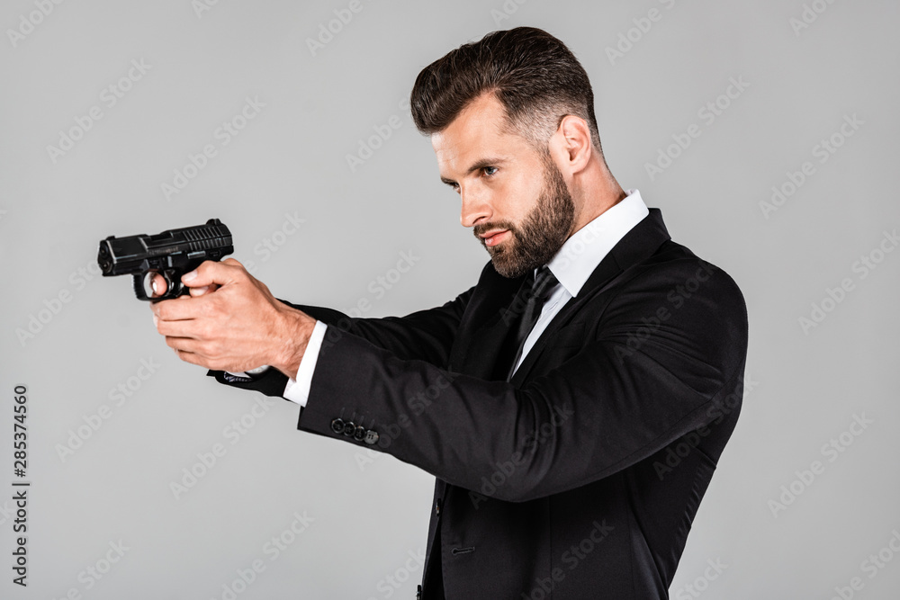 handsome agent in black suit aiming gun isolated on grey
