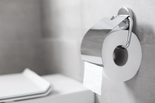 Roll Of White Toilet Paper Hanging On Metal Toilet-paper Holder At Restroom