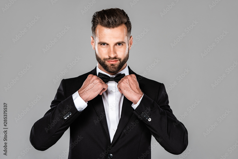 Fototapeta elegant smiling man in black suit fixing bow tie isolated on grey