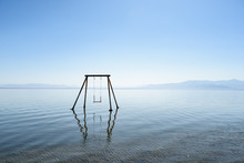 Abandoned Swing In The Water A...