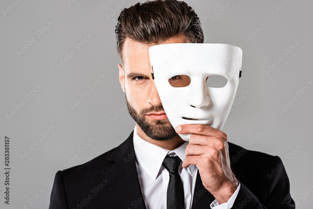 Fototapeta serious handsome businessman in black suit taking off white mask isolated on grey