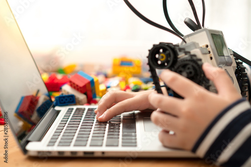 Photographie  Closeup : hands of preteen / teenage boy codes Lego Mindstorms on his computer laptop, other hand holds robot build for school project