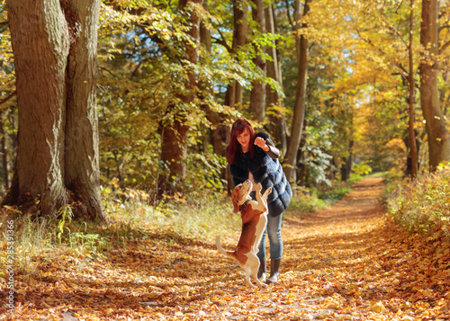 Young woman walking with a dog in the autumn park. Wallpaper Mural