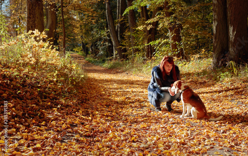 Photo  Young woman walking with a dog in the autumn park.