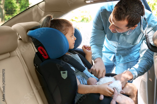 Cuadros en Lienzo Father buckling his little daughter in car safety seat