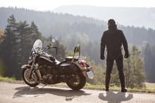 Back View Of Tall Athletic Sportive Muscular Motorcyclist In Black Leather Clothing Standing At Cruiser Powerful Motorbike, On Foggy Background Of Sunny Green Spruce Forest Under Bright Sky.