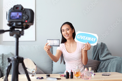 Asian beauty blogger announcing giveaway while recording video at home Wallpaper Mural