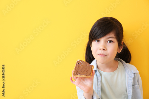 Fotografiet  Funny little girl eating tasty toast with chocolate spreading on color backgroun
