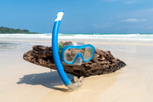 Snorkeling Mask On The Dry Tree Wet With Beautiful Blue Sea And Island In Sunny Day Of Summer. Snorkeling Equipment On A Wooden Log Sticking Out Of The Sand. Beach With White Sand.