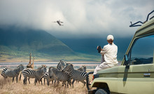 Woman Tourist On Safari-tour In Africa, Traveling By Car In Tanzania, Watching Wild Animals And Birds In The National Park Ngorongoro