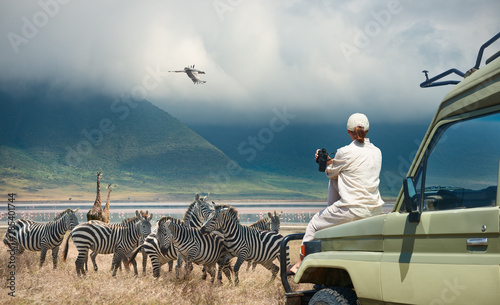 Woman tourist on safari-tour in Africa, traveling by car in Tanzania, watching w Wallpaper Mural