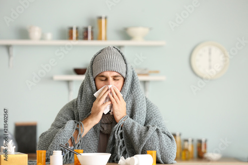 Photo  Sick man sitting at kitchen table
