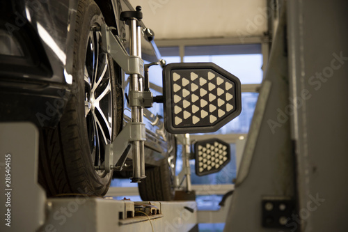 Photo Car on stand with sensors on wheels for wheels alignment camber check in worksho