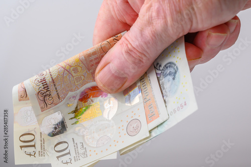 Photo Paying for goods or services with British pound  notes  white background