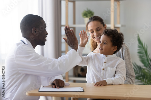 Happy cute child boy give high five to african pediatrician Fototapet
