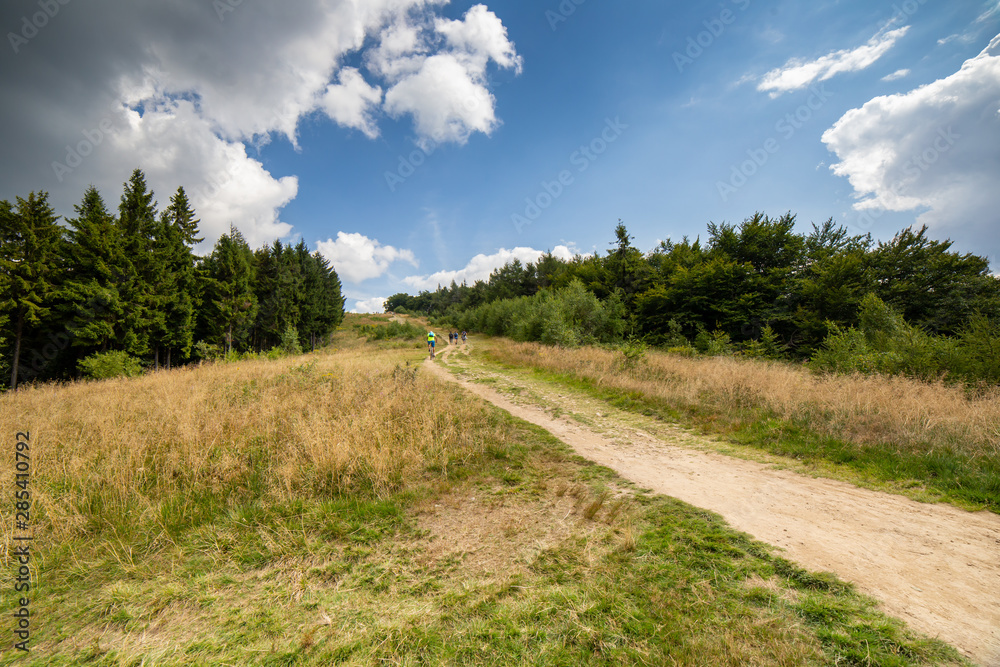 Tourists and bikers on mountain trail in Polish Beskid Mountains to Jaworzyna Krynicka near Krynica in Poland