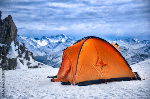 Photo Red orange tent in a solitary bivouac in the snow atop a mountain (Mont Blanc in