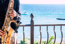 Closeup Of Music Artist Saxophonist  Touching His Instrument In The Restaurant Or Bar With The Beach Or The Sea Or Ocean In The Background