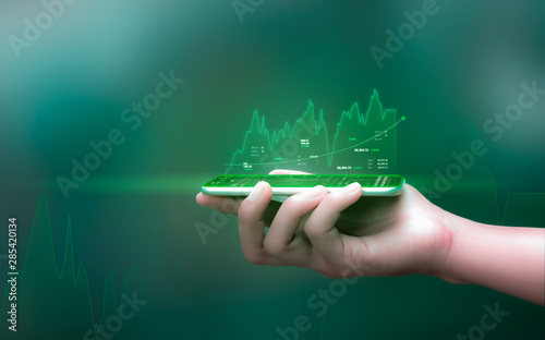 Fotografía  Businessman holding smartphone and showing holographic graphs and stock market statistics gain profits