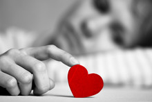 Sad And Upset Girl Is Touching Red Heart With Finger